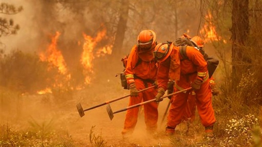 Sept. 12, 2015: A California Department of Corrections and Rehabilitation inmate work crew builds a containment line ahead of flames from the Butte Fire, near Sheep Ranch, Calif.
