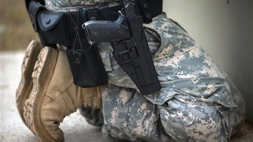 Sept. 29, 2015: A member of the 139th Military Police Company kneels with his holstered 9mm Beretta M9 during a qualifying exercise at a small arms range in Fort Stewart, Ga.