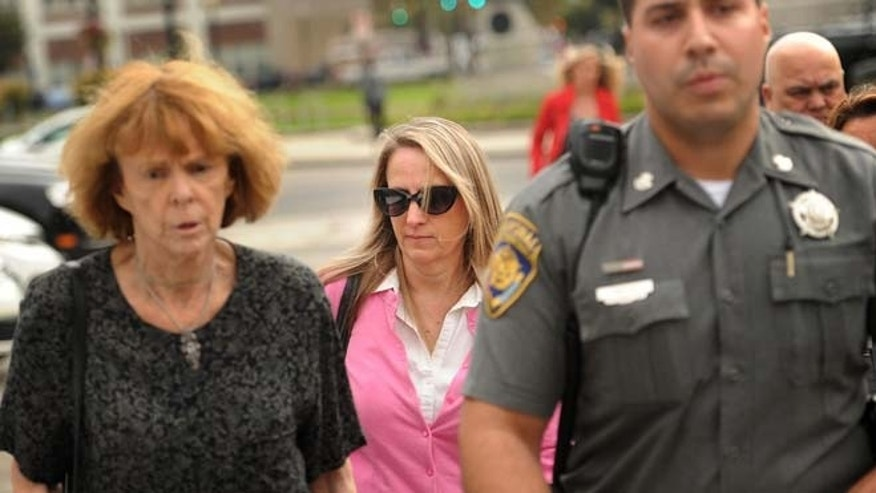 Oct. 13: Jennifer Connell, center, is escorted to her car by marshals after her lawsuit against her Westport nephew was found in his favor in Superior Court in Bridgeport, Conn.