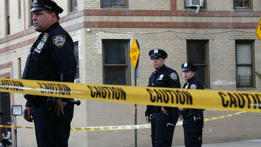 Oct. 15, 2015: Police officers stand guard near an apartment building in the Bronx borough of New York.