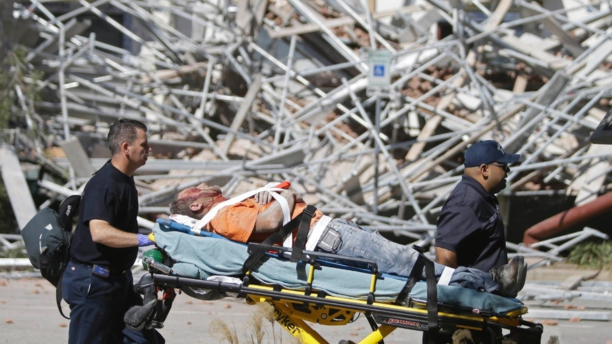 Oct. 16, 2015: Emergency personnel tend to an injured worker at a scaffolding collapse at a building under construction in Houston.