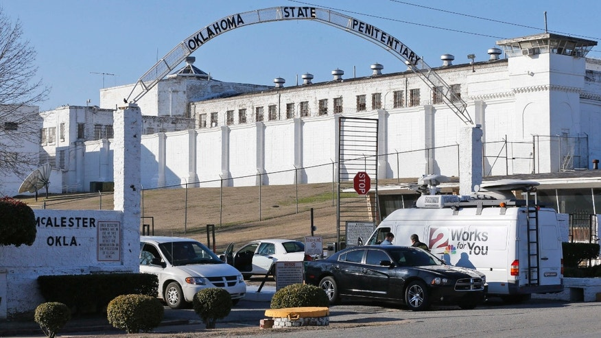 FILE - In this Jan. 15, 2015, file photo, a news van arrives at the front gate of the Oklahoma State Penitentiary for the scheduled execution of Charles Warner in McAlester, Okla.