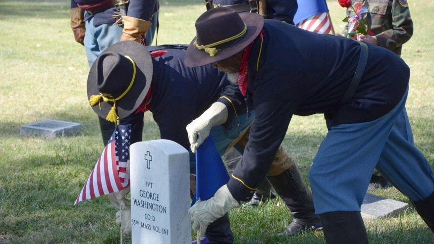 Oct. 3, 2015: Two members of the Buffalo Soldiers of the American West place flags beside the new headstone for Pvt. George Washington in Roselawn Cemetery in Pueblo, Colo.