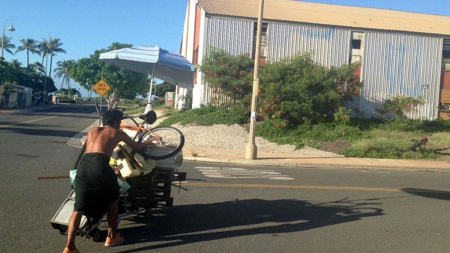 Oct. 8, 2015: A homeless man who had been living in a large encampment in the Kakaako neighborhood of Honolulu pushes his bleongings away from the camp as city officials sweep the area.