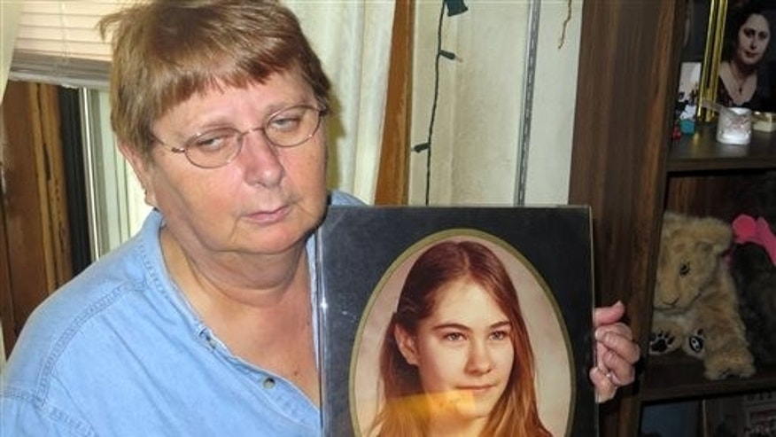 In this Oct. 16, 2015 photo, Carolyn Tousignant hold a photo of her daughter Carrie Ann Jopek, at her home in Milwaukee, Wis. (AP Photo/Greg Moore)