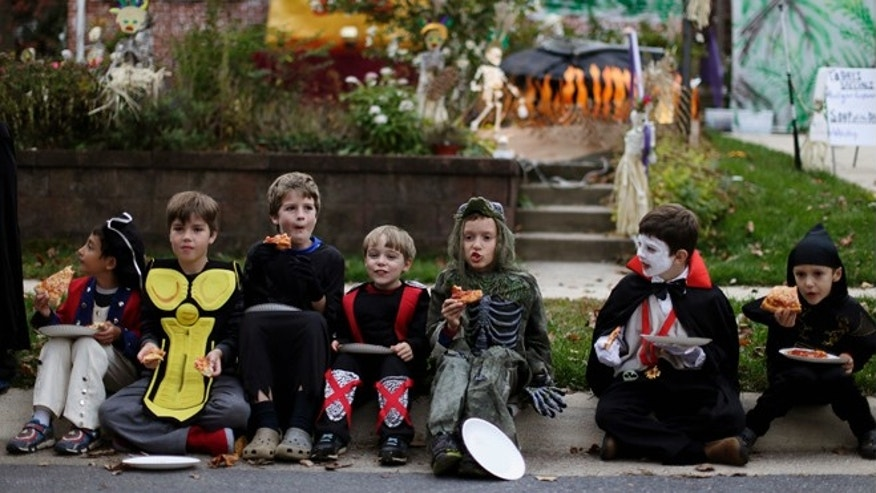 Oct. 31, 2014: Children dressed in costumes eat pizza on Halloween.