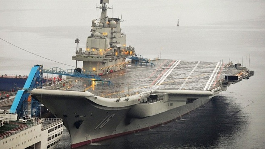 FILE 2012: China's first aircraft carrier, which was renovated from an old aircraft carrier that China bought from Ukraine in 1998, is seen docked at Dalian Port.