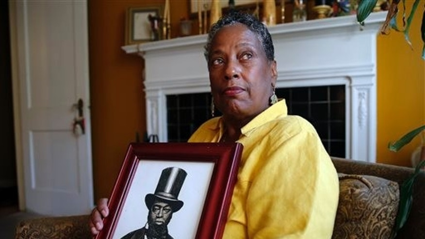 Ocea Thomas poses for a portrait with a picture of her ancestor Samuel Burris.