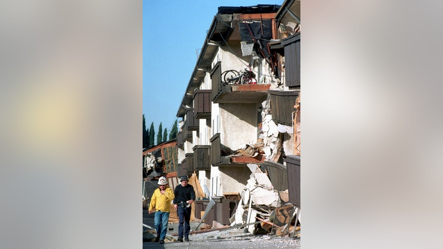 FILE - In this Jan.17, 1994, file photo, rescue workers walk past the Northridge Meadows Apartments that collapsed during the earthquake in Los Angeles.
