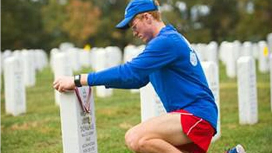 Seamus Donahue, 18, places his Marine Corps Marathon finisher's medal on the grave of his father, Maj. Michael Donahue, at Arlington National Cemetery on Oct. 25, 2015. Seamus ran the marathon in honor of his father who was killed in Kabul, Afghanistan on Sept. 16, 2014.