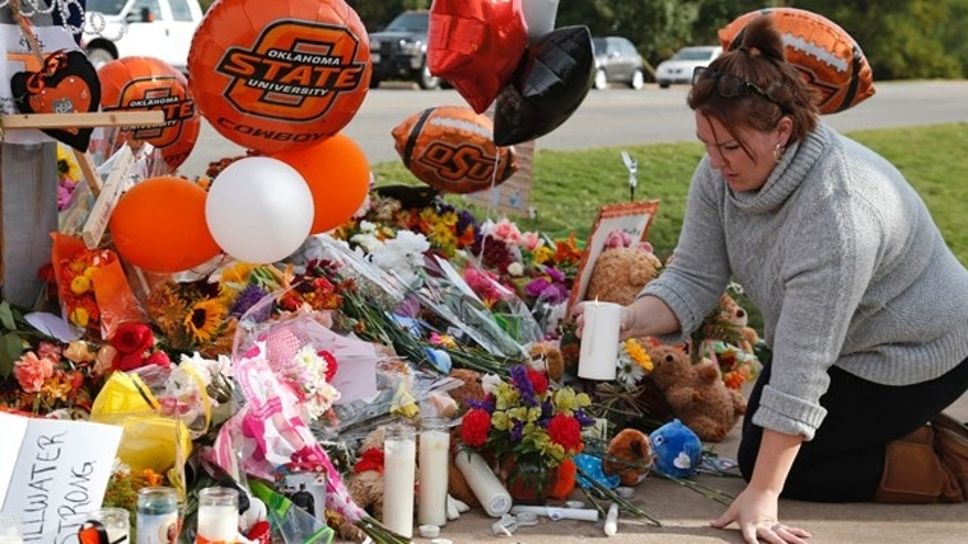 Oct. 26, 2015: Stefanie Alexander, who witnessed the Saturday homecoming parade crash, places a candle at a makeshift memorial to the victims in Stillwater, Okla. (AP Photo/Sue Ogrocki)