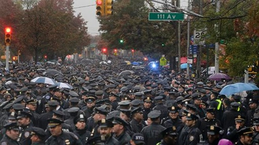 Hundreds of New York police officers gather in the street outside a church for the funeral of Officer Randolph Holder, Wednesday, Oct. 28, 2015, in New York. (AP Photo/Julie Jacobson)