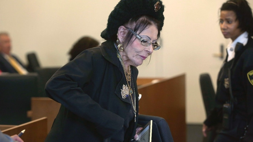 Oct. 28, 2015: Witch priestess Lori Sforza holds a certificate of baptism as she returns to her seat after testifying in district court in Salem, Mass.