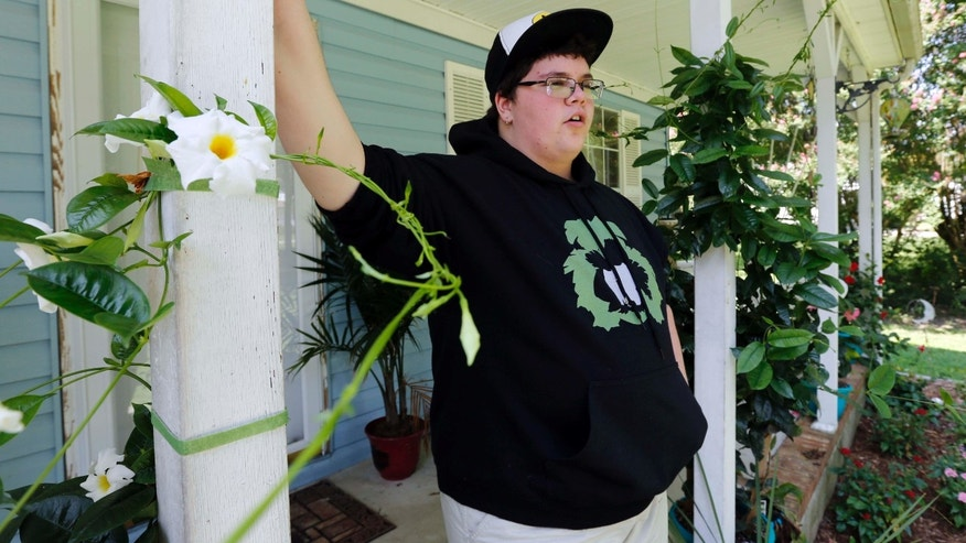 FILE - In this Aug. 25, 2015 file photo, Gavin Grimm leans on a post on his front porch during an interview at his home in Gloucester, Va.