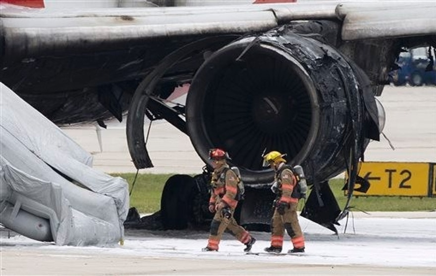 Firefighters walk past the burned engine. (AP Photo/Wilfredo Lee)