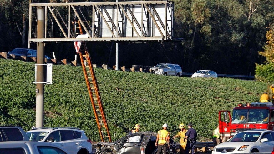 Oct. 30, 2015: he body of a driver ejected when his car rolled over several times on southbound Interstate 5 is seen where it landed on an overhead freeway sign north of downtown Los Angeles.