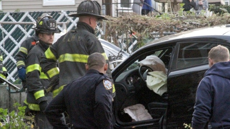 Sat. 31, 2015: First responders examine an automobile after its driver lost control and plowed into a group of trick-or-treaters in New York. Three people were killed, including a 10-year-old girl. (AP Photo/David Greene)