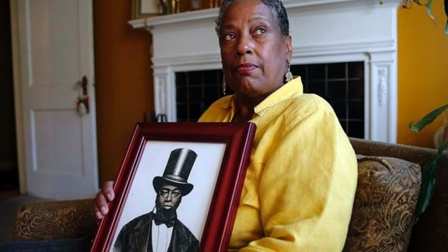 Oct. 20: Ocea Thomas poses for a portrait with a picture of her ancestor Samuel Burris that she received a phone call this weekend letting her know that Gov. Jack Markell would pardon Burris, a free black man and conductor on the Underground Railroad who died in 1863.