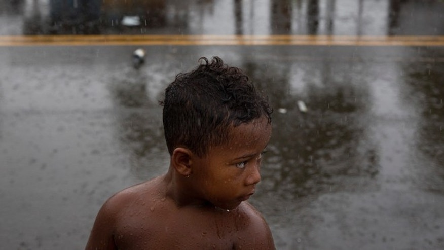A boy stands in the rain in front of makeshift tents at a homeless encampment in the Kakaako district of Honolulu.