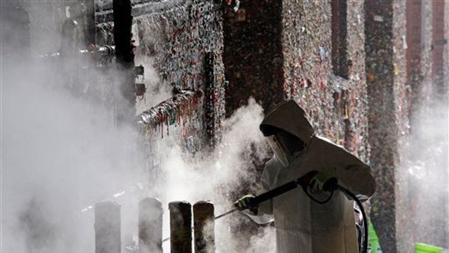 "A worker uses a powerful steam cleaner to work decades of gum off Seattle's ""Gum Wall."""