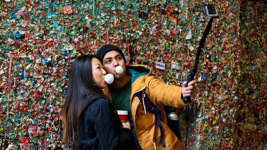 "Nov. 9, 2015: Jessica Wang, left, and Michael Teylan, both of Los Angeles, use a selfie stick at Seattle's ""gum wall"" at Pike Place Market."