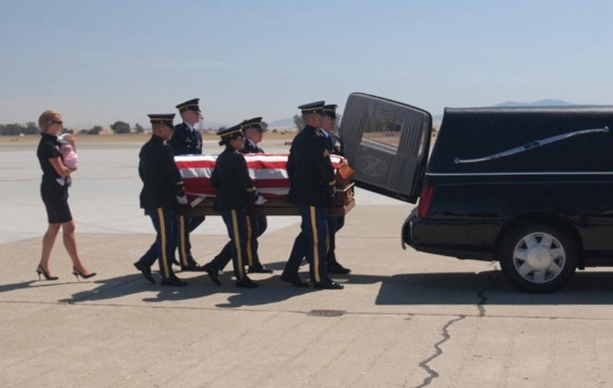 For Lisa Hallett, shown here carrying baby Heidi as her husband's casket is loaded into a hearse, the project was a way to heal.