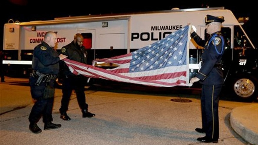 Nov. 10, 2015: In this provided by the Milwaukee Police Department, officers, from left, Jedidiah Thompson, Jutiki X and Joel Rossman fold a flag they recovered after it was set on fire by a protester outside the Republican presidential debate in Milwaukee.