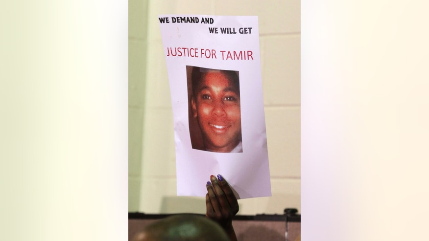 FILE- This Dec. 8, 2014 file photo shows a person holding up a sign for justice for Tamir Rice during a news conference in Cleveland.