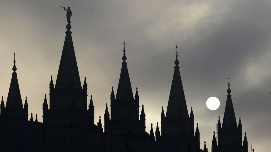 FILE - In this Feb. 6, 2013, file photo, the angel Moroni statue, silhouetted against a cloud-covered sky, sits atop the Salt Lake Temple, at Temple Square, in Salt Lake City.