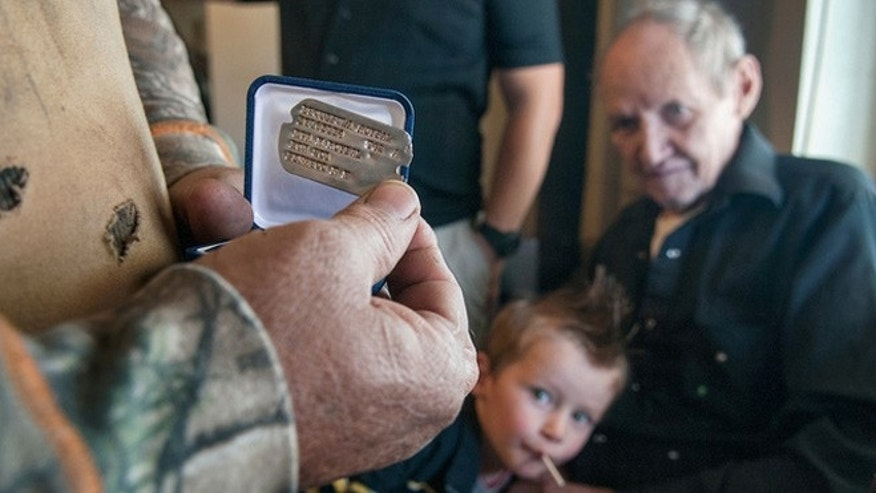 Joe Roy Roybal, right, with his great-grandson Albianjames Valdezhern, 2, watches as his brother Ivan Roybal pulls out the dog tag of their uncle Esquipula Roybal. (Eddie Moore/Albuquerque Journal)
