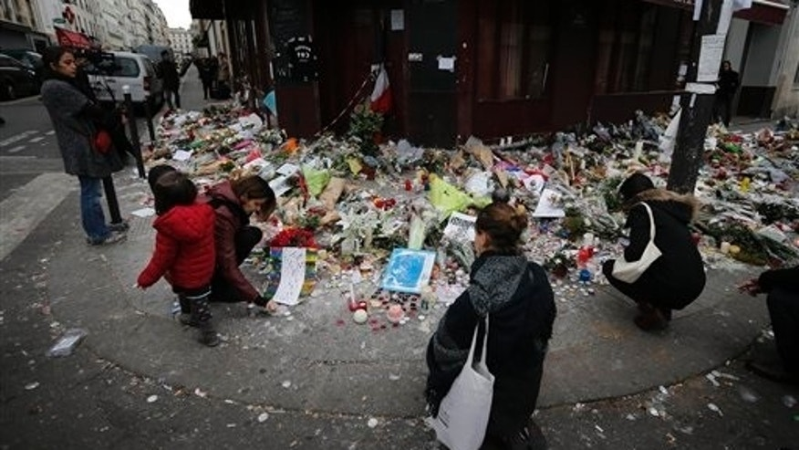 People lay flowers and candles in front of  the restaurant Le Carillon, one of the establishments targeted in Friday's gun and bomb attacks, in Paris, Monday, Nov. 16, 2015. French police raided more than 150 locations overnight as authorities released the names of two more potential suicide bombers involved in the Paris attacks one born in Syria, the other a Frenchman wanted as part of a terrorism investigation. (AP Photo/Frank Augstein)