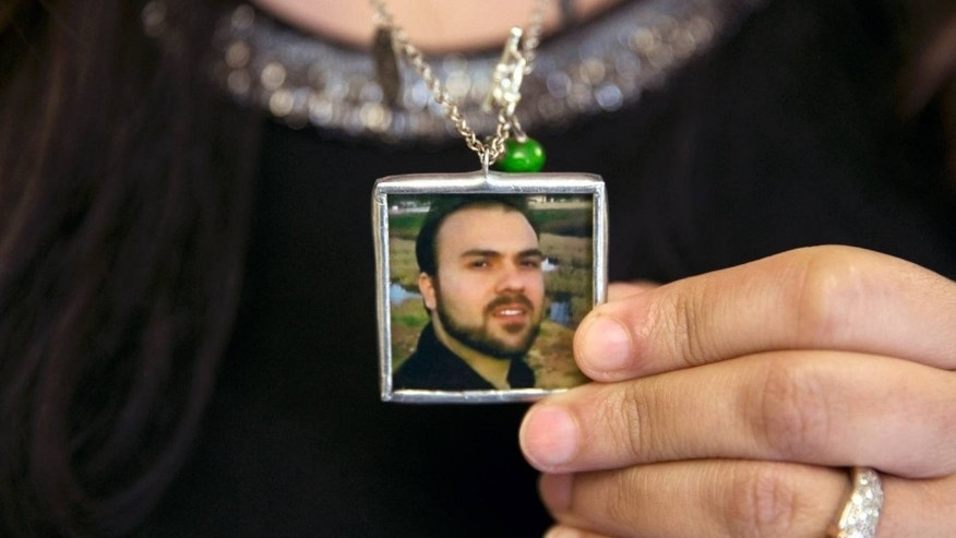 Naghmeh Abedini holds a necklace with a photograph of her husband, Saeed.