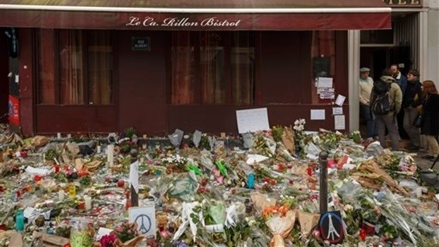 Flowers lay outside the Carillon cafe, a site of last Friday's attacks, in Paris, Tuesday, Nov. 17, 2015. France made an unprecedented demand on Tuesday for its European Union allies to support its military action against the Islamic State group as it launched new airstrikes on the militants' Syrian stronghold, days after attacks in Paris linked to the group killed at least 129 people. (AP Photo/Daniel Ochoa de Olza)