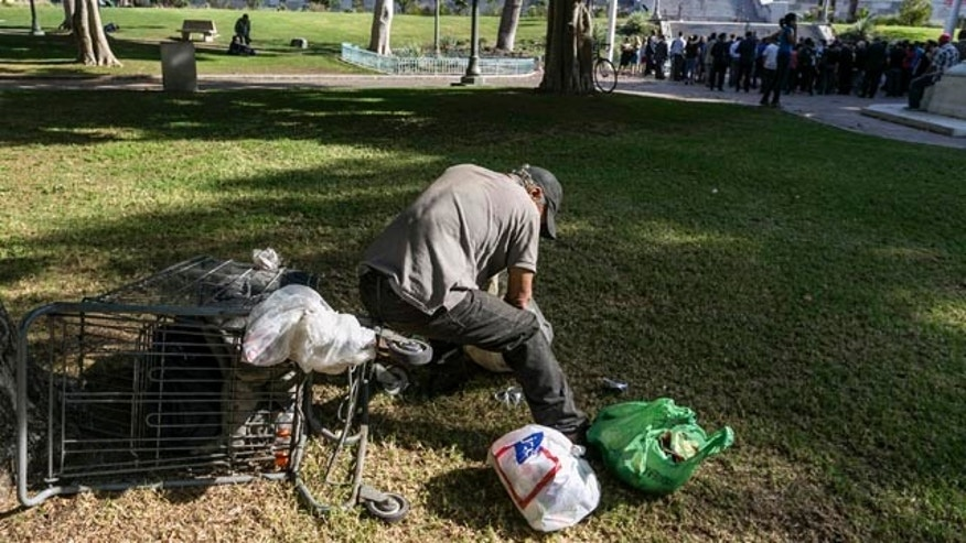 Sept. 22, 2015: A person sorts recyclable cans on the south lawn of City Hall in Los Angeles. Los Angeles officials gathered in the background said they will declare a state of emergency on homelessness and proposed spending $100 million to reduce the number of people living on city streets, as homeless people dozed nearby on a lawn and sidewalks. (AP Photo/Damian Dovarganes)