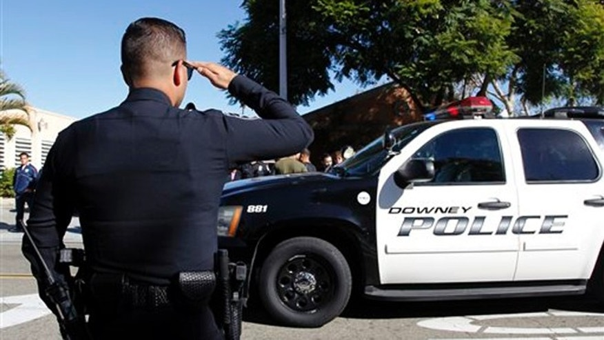 """Nov. 19, 2015: An unidentified police officer salutes as Los Angeles County Coroner transports the body of Downey police Officer Ricardo """"Ricky"""" Galvez in Downey, Calif."""