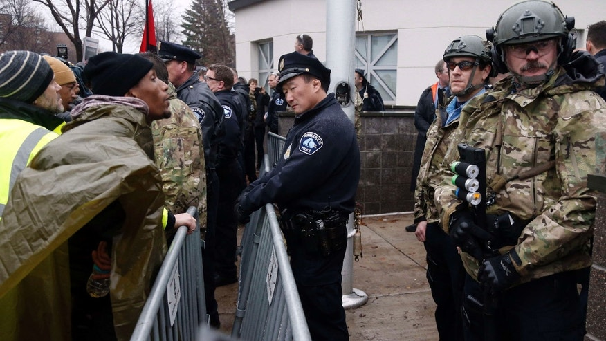 Nov. 18, 2015: A Black Lives Matter supporter, left, talks to Minneapolis police guarding the Fourth Precinct entrance in Minneapolis.
