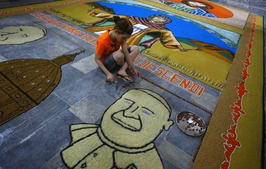 An Iraqi child works on a temporary mosaic of Pope Francis' face made from wheat, beans and lentils in Alqosh, a village of some 6,000 inhabitants about 31 miles north of Mosul, northern Iraq. (AP)