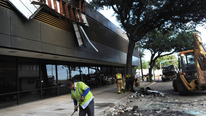 Nov. 20, 2015: Workers clean up debris after 47-year-old woman hit the gas instead of the brake and drove off the third floor of the Prosperity Bank parking garage in Abilene, Texas.