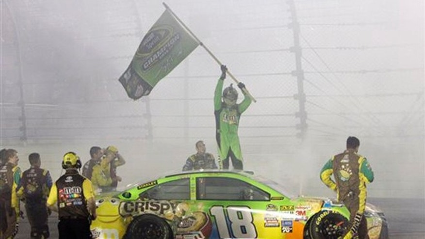 Nov. 22, 2015: Kyle Busch (18) celebrates after winning the NASCAR Sprint Cup Series auto race and the season title at Homestead-Miami Speedway in Homestead, Fla.