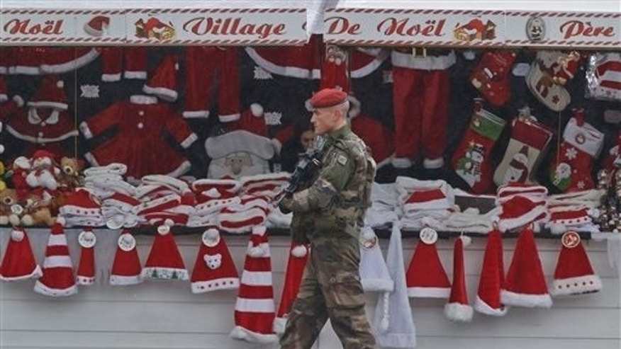 A soldiers patrols at the Christmas market along the Champs Elysees avenue in Paris, Tuesday, Nov. 24, 2015. French authorities on Tuesday questioned a top suspect linked to attackers who terrorized Paris, while Belgium's capital remained locked down under threat of a possible similar attack. (AP Photo/Michel Euler)