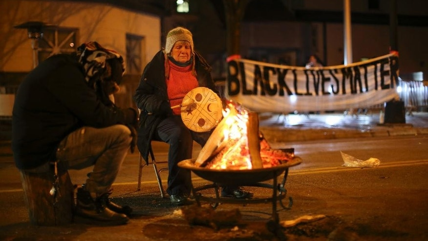 People warm themselves as they demonstrate since the Nov. 10 shooting of 24-year-old Jamar Clark, in front of the Minneapolis Police 4th Precinct on Tuesday, Nov. 24, 2015. Minneapolis police were searching Tuesday for three white males suspected of shooting at five Black Lives Matter demonstrators, while the family of a black man who was fatally shot by a city police officer called for the dayslong protests outside of the police precinct to end. (Jeff Wheeler/Star Tribune via AP)