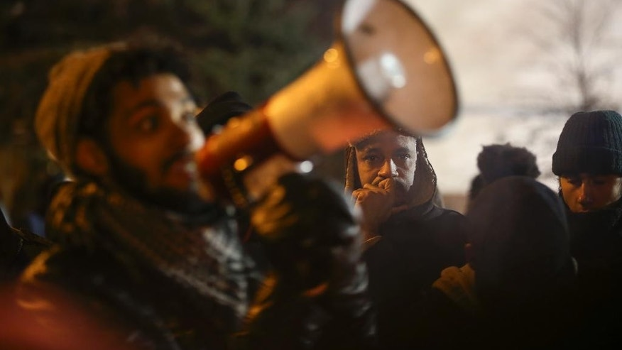 People gather around a demonstrator speaking about his encounter with attackers who were shooting at five protesters near the Minneapolis Police 4th Precinct earlier in the night, as protesters gather in front of the precinct in Minneapolis on Tuesday, Nov. 24, 2015. Minneapolis police were searching Tuesday for three white males suspected of shooting at five Black Lives Matter demonstrators, while the family of a black man who was fatally shot by a city police officer called for the dayslong protests outside of the police precinct to end. (Jeff Wheeler/Star Tribune via AP)