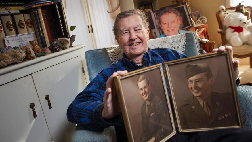 Hugh Montgomery, 91, a former CIA and OSS officer who parachuted into Normandy on D-Day with the 82nd Airborne., holds two photographs of himself in 1943, at his McLean, Va., home, Tuesday, Nov. 24, 2015. Montgomery went behind enemy lines for the OSS, where he was among the first Americans to come upon the Buchenwald concentration camp. After returning to Harvard to earn his PhD and teach, he joined the newly formed CIA, where he led spying operations against the Soviets for decades, doing tours in Rome,  Paris and Moscow. A photo of his late wife Annmarie is behind him. (AP Photo/Cliff Owen)
