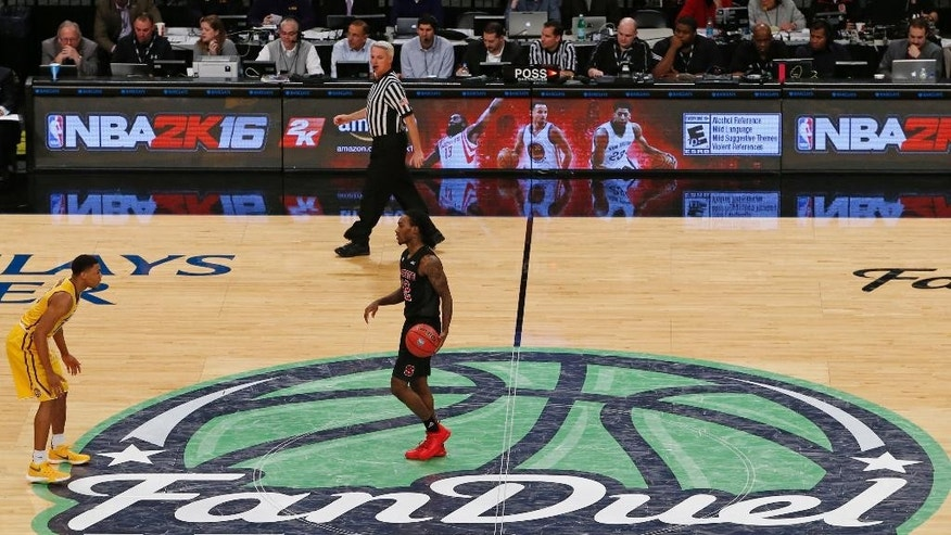 North Carolina State guard Anthony Barber (12) dribbles the ball across the FanDuel logo during the first half of an NCAA college basketball game in the Legends Classic, Tuesday, Nov. 24, 2015, in New York. FanDuel, which sponsored the Legends Classic, and DraftKings are due back in a New York court Wednesday after the state attorney general filed papers seeking to stop the sites from operating, while the sites have argued operations are legal. (AP Photo/Kathy Willens)