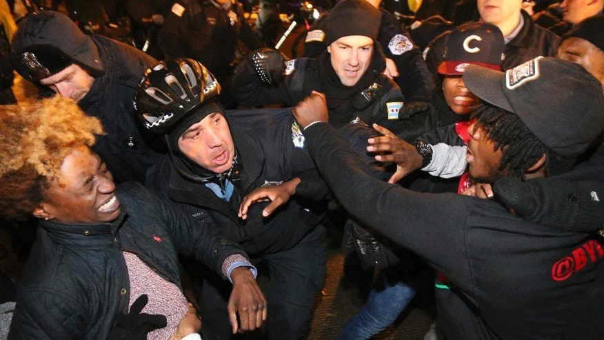 Chicago police scuffle with protesters in Chicago, on Tuesday, Nov. 24, 2015. White Officer Jason Van Dyke, who shot Laquan McDonald 16 times last year, was charged with first-degree murder Tuesday, hours before the city released a video of the killing. (Nuccio DiNuzzo/Chicago Tribune via AP) MANDATORY CREDIT CHICAGO TRIBUNE; CHICAGO SUN-TIMES OUT; DAILY HERALD OUT; NORTHWEST HERALD OUT; THE HERALD-NEWS OUT; DAILY CHRONICLE OUT; THE TIMES OF NORTHWEST INDIANA OUT; TV OUT; MAGS OUT; NO SALES