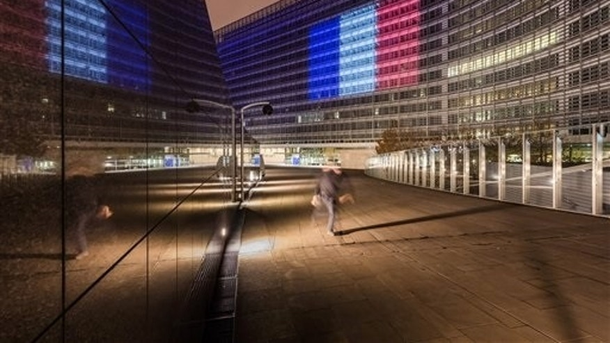 A man walks by the EU Commission headquarters illuminated with the colors of the French national flag in solidarity with France after the terror attacks in Paris, in Brussels on Sunday, Nov. 15, 2015. (AP Photo/Geert Vanden Wijngaert)