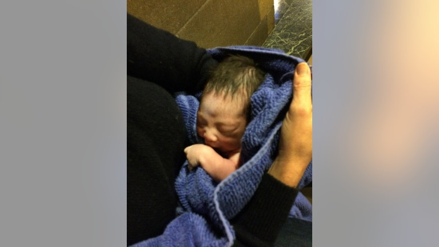 In this Monday, Nov. 23, 2015 photo provided by Paul Cerni, an unidentified woman holds a baby at the Holy Child of Jesus Church in the Richmond Hill section of Queens, New York. A church custodian found the abandoned newborn Monday in the church nativity scene. New York has a so-called safe haven law that says a newborn can be dropped off anonymously at a church, hospital, police or fire station without fear of prosecution. But the law, known as the Abandoned Infant Protection Act, requires that the child be left with someone or for authorities to be called immediately. Police are searching for the mother. (Paul Cerni via AP)