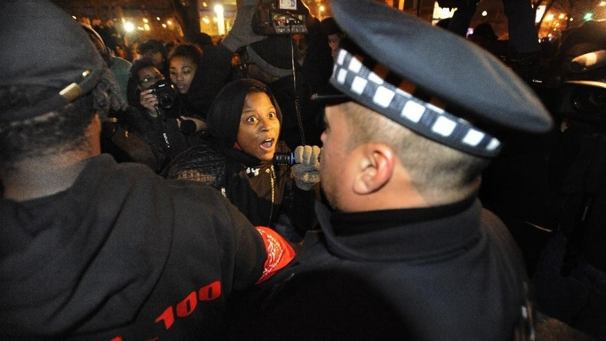 A protester yells at Chicago police officers outside the District 1 central headquarters at 17th and State streets, Tuesday, Nov. 24, 2015, in Chicago, during a protest for 17-year-old Laquan McDonald, who was fatally shot and killed in October 2014. Chicago police Officer Jason Van Dyke was charged Tuesday with first-degree murder in the killing. (AP Photo/Paul Beaty)
