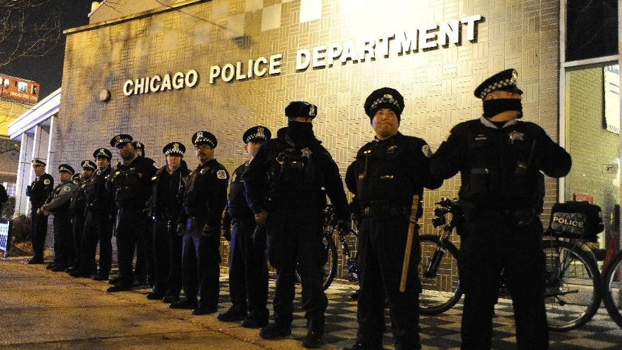 Chicago police officers line up outside the District 1 central headquarters at 17th and State streets, Tuesday, Nov. 24, 2015, in Chicago, during a protest for 17-year-old Laquan McDonald, who was fatally shot and killed in October 2014. Chicago police Officer Jason Van Dyke was charged Tuesday with first-degree murder in the killing. (AP Photo/Paul Beaty)