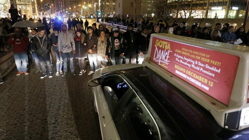 Protesters block rush hour traffic along the Michigan Ave. bridge over the Chicago River Wednesday, Nov. 25, 2015, in Chicago, the day after murder charges were brought against police officer Jason Van Dyke in the killing of 17-year-old Laquan McDonald. (AP Photo/Charles Rex Arbogast)